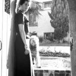 Joan Szukalski in doorway with dog